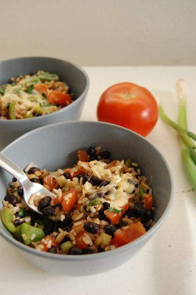 100 gram bruine rijst 1 paprika  240 gram zwarte bonen  3 bosuitjes 3 teentjes knoflook 2 tomaten 1 theelepel paprikapoeder 1/2 theelepel chilipoeder 1/2 theelepel komijn 50 gram geraspte jonge- of cheddar kaas 1 eetlepel  koriander  Kook de rijst. ui + look. Bak dit. Snijd de tomaten in blokjes en voeg deze ook toe  met de uitgelekte bonen en de komijn, chili- en paprikapoeder. Als de rijst klaar is, kun je deze toevoegen. Roer alles .Doe de rijst in een kom, verdeel er wat geraspte kaas