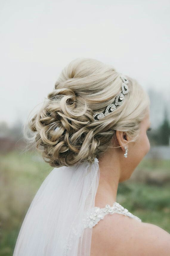 Wedding updo with headband and veil underneath.
