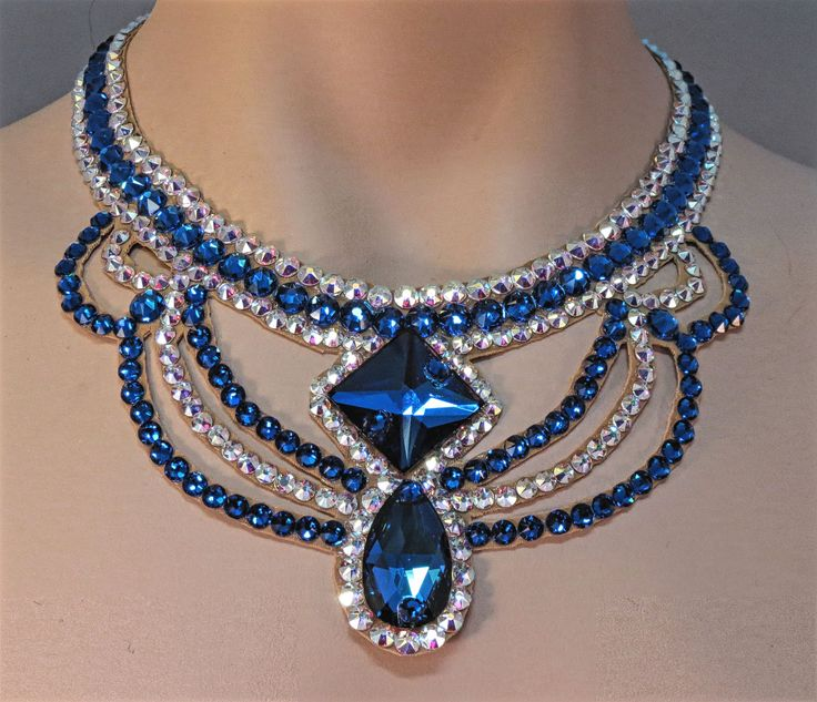 This necklace was created with Crystallized™ Swarovski Elements crystals. The necklace has a large pear and square shaped blue crystals in the front with blue and ab clear swirls creating this dramati