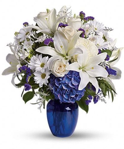 Beautiful in Blue-Brighten the home with the peace and beauty of a bright blue sky. This beautiful bouquet pairs pure white flowers with deep blue blooms in a gorgeous blue glass vase. Blooms such as blue hydrangea, crème roses, graceful white oriental lilies, white alstroemeria, a white disbud mum, purple statice and lavender limonium are accented by seeded eucalyptus and salal in a stunning cobalt blue glass vase. #CentralSquareFlorist #CambrideFlowers #SympathyFlowers