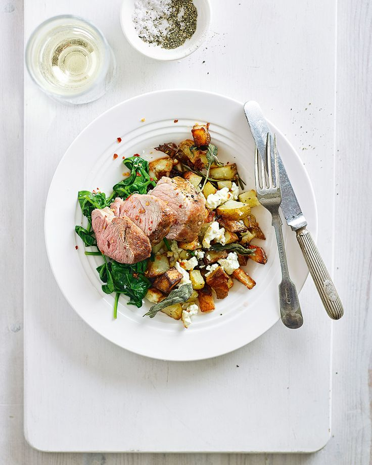 Pork tenderloin is cooked nestled among crispy potatoes, feta and herbs in this easy midweek recipe.