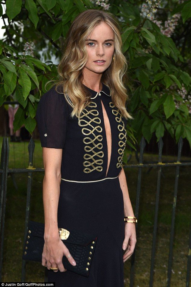 Cressida dazzled in am embroidered black and gold gown slashed low at the front and open a...