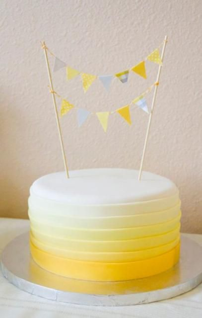 Round birthday cake with cicular yellow gradient bands and poles with triangle flags.JPG