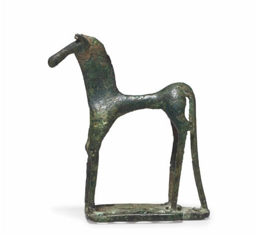 Greek bronze horse, Geometric period, mid 8th century B.C. Standing four-square with its legs and tail joined to a shallow openwork integral plinth perforated with triangles, the stylized animal with a narrow tubular body curving up to the croup, with bulging haunches and thin elongated tail and legs, the knee joints bulging, the thin neck with a sharp broad mane crest, the head with short upturned ears, a sharp pointed poll and a long cylindrical muzzle, 8.6 cm high. Private collection