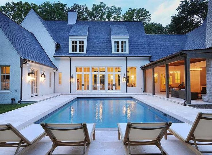 Chic backyard features long steps into pools lined with teak adjustable pool loungers.