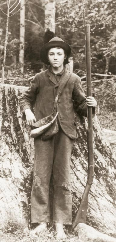 A young boy posing with a hog rifle. He is wearing a powder horn and pouch. Photo taken around 1906.