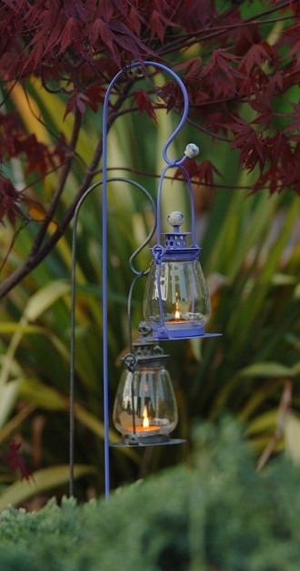 small candle-lit lanterns on a shepherd's hook in the garden