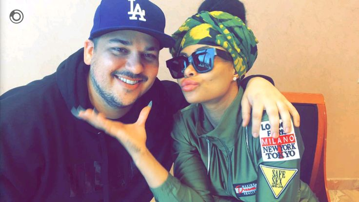 "Either Rob Kardashian and Blac Chyna are engaged, or the couple is toying with our already fragile emotions. Chyna took to Instagram early Tuesday, April 5 to post a photo of Rob cheesing as she lovingly touches his face. That's sweet, but we've come expect moments like that from the lovebirds. The big difference here is that Chyna is rocking a gigantic diamond ring on her left hand's ring finger and the caption says, ""YES!.!.!"" There is only one way to interpret that, right? It's starting…"