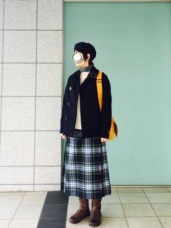 キルトスカートを合わせた上品な着こなしも素敵。ネイビーのピーコートにネイビーが入ったチェックのスカートがピッタリ。ブーツと合わせたコーデは冬ならではなので、丈感を意識して楽しみたいですね。