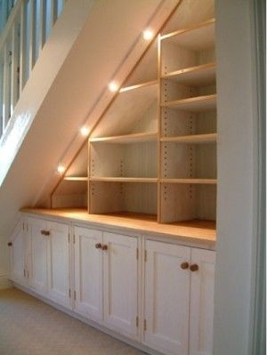 under basement stairs by MarylinJ. Could do a couple or four (more possibly) drawers in shelve spaces Like this idea but also like having a seating area with a table behind that too. Lots of ideas!
