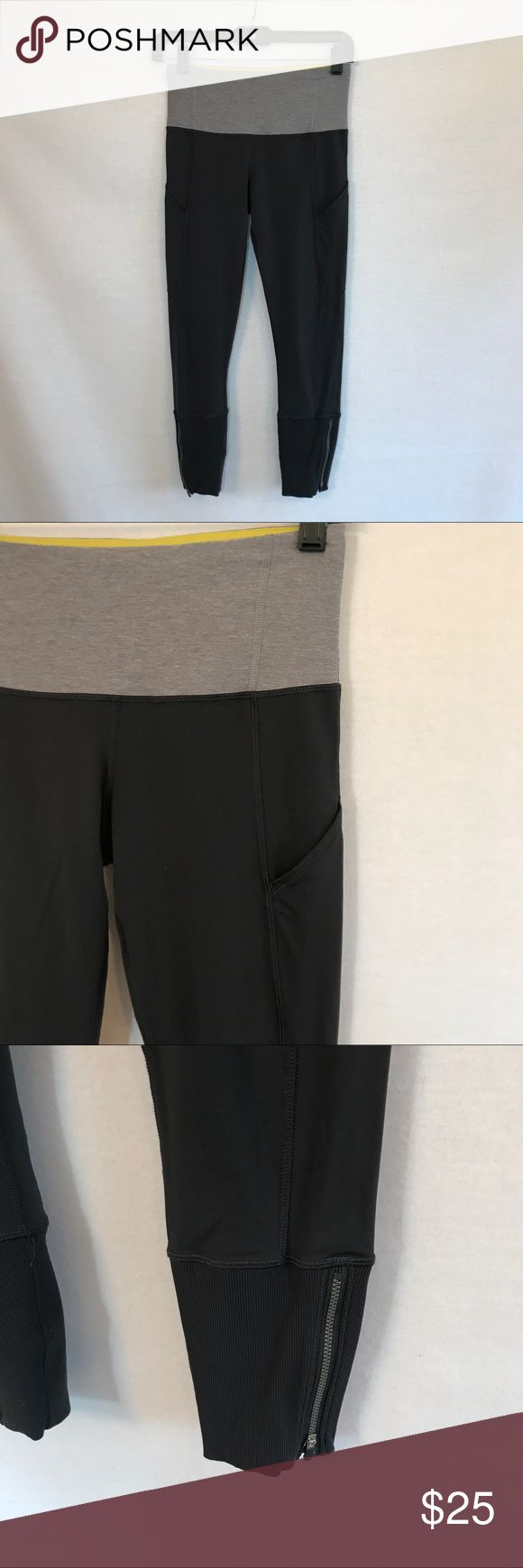 """Lululemon size four active crops gray zip bottom Great active leggings from Lululemon. Dark and light gray exterior with pop of bright yellow on the inside. Zipper at the bottom and thin open pockets on the side. Diagonal zip pocket on the back. Leggings still fully functional - decorative seaming on the back has pulled out. See photos. Size located inside yellow waistband pocket.   waist: approx 12.5"""" inseam: approx 24"""" length: approx 32"""" lululemon athletica Pants Leggings"""