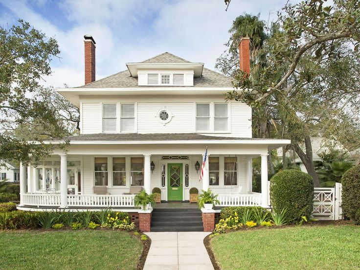 White Home With A Wraparound Porch And Green Door