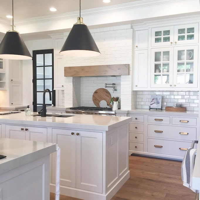 white kitchen with grand architecture, white brick range hood framing with rustic wood detail, silver hardware, black faucet and pendants   House of Jade Utah Parade of Homes