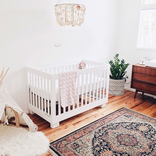 nursery - wood floors, white walls, chandelier, persian rug, and mid century furniture.