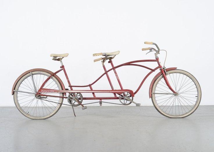 """Une bicyclette tandem vintage Huffy Daisy. Ce vélo une vitesse fabriqué entre 1957 et 1963 était connu sous le nom de """"Big Red"""". Le cadre métallique dispose d'un tube supérieur au design abaissé pour le siège arrière. Le vélo est muni de deux selles blanches, de poignées blanches et de pneus à flanc blanc. Equipé d'un frein avant et d'un frein à rétropédalage pour l'arrière. Le prix: 250$US."""