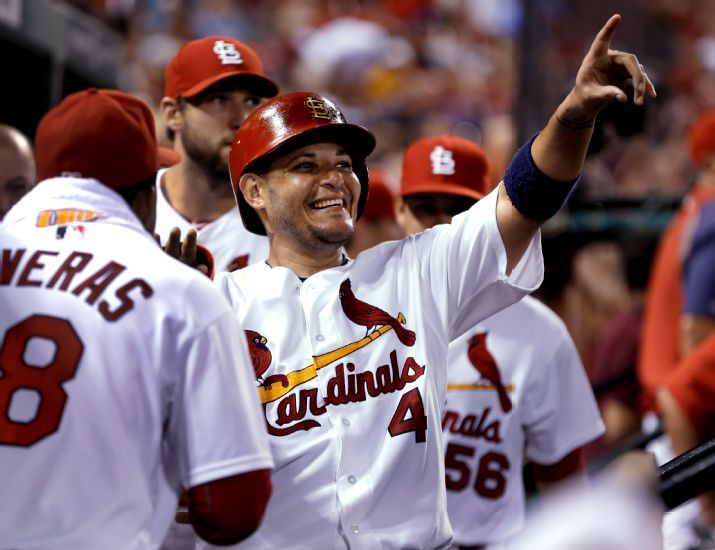 St. Louis Cardinals' Yadier Molina, right, smiles and points from the dugout as he watches a replay of him scoring during the fourth inning ...