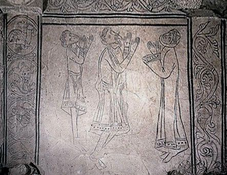 """Zachowany fragment pierwszej, jednonawowej kolegiaty - tzw. płyta wiślicka nazywana również płytą orantów, pochodzi z okresu 1175-1177, jest wykonana z jastrychu i zdobiona rysunkami na dwóch polach otoczonych bordiurą. Rysunki przedstawiają postaci z rękami wzniesionymi w modlitewnym geście, stąd określenie """"płyta orantów"""". Mężczyzna z brodą identyfikowany jest jako fundator świątyni Kazimierz Sprawiedliwy, pozostałe osoby jako jego żona Helena i syn Bolesław."""