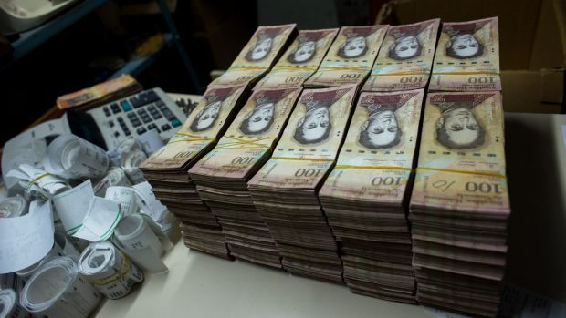 Stacks of banknotes are piled on a desk in a bakery in Caracas. Once one of the world's strongest currencies, the ...