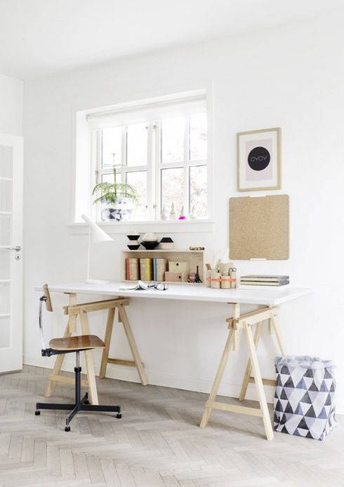 skandynawskie białe biurko na drewnianych kozłach,drewniane nowoczesne krzesło na metalowym krzyżaku i korkowe detale w aranzacji prostego domowego biura,