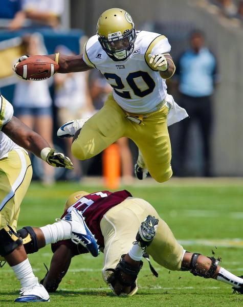 Georgia Tech running back David Sims leaps over Elon defensive lineman Gary Coates in Atlanta Saturday. (John Bazemore/AP)