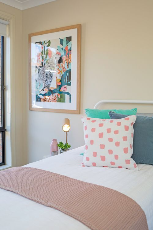 kids bedroom, single bed, white metal bed frame, white bedding, colourful cushions, pink, aqua, blue, parrot artwork, timber lamp