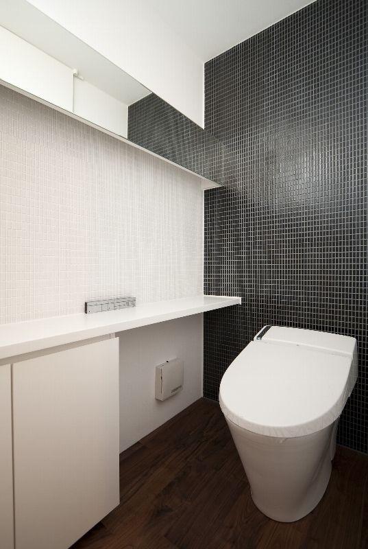 白と黒のタイルを張った壁。<br /> 他の部屋とデザインを統一しています。<br /> 壁の端から端まで鏡を通すことで、空間の広がりを感じます。 専門家:辻 秀易が手掛けた、トイレ(稜線のいえ)の詳細ページ。新築戸建、リフォーム、リノベーションの事例多数、SUVACO(スバコ)