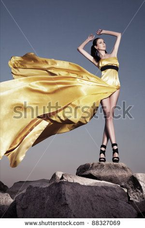 Beautiful Woman In Evening Dress Standing On A Rock Blown By The Wind Fashion Photo Via Shutterstock