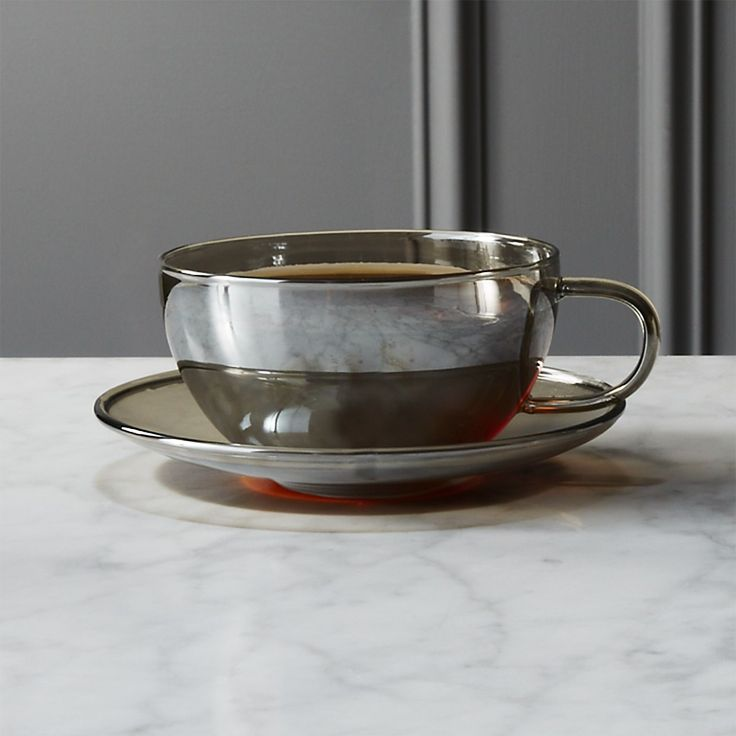 Shop fool's gold cup with saucer. Handmade of glass, modern silhouette sits low on matching saucer. Finished with a transparent smoke metallic tint, duo adds shine to coffee or tea. Beautiful on display. fool's gold cup with saucer is a CB2 exclusive.
