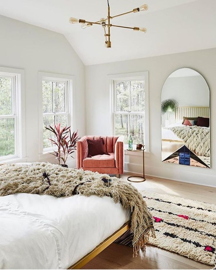 Gorgeous bedroom with architectural ceiling, fur throw on bed, patterned rug, and large mirror