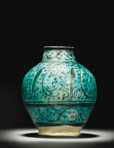 A Raqqa ovoid-form pottery jar, Syria, first half 13th century of baluster form with a globular body and tall, slightly inverted neck, decorated in black under a turquoise glaze with a row of stylised birds amidst flowing vegetal scrolls, between bands with spiraling tendrils 27.5cm. height.