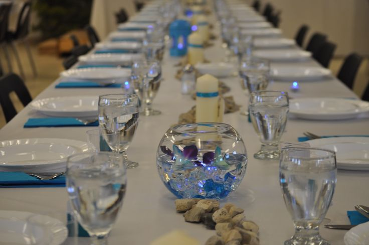 Fish bowl with white/blue stones, with blue LED  tealight in bottom, filled with water and floating blue orchids