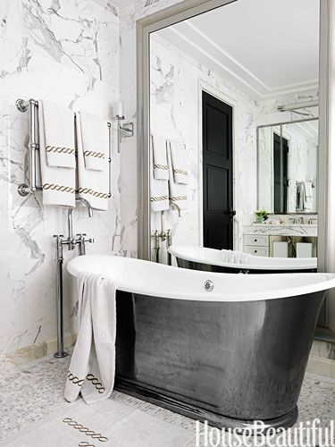 In the master bath, a floor-to-ceiling mirror is a dramatic backdrop for the freestanding cast-iron tub by Waterworks.