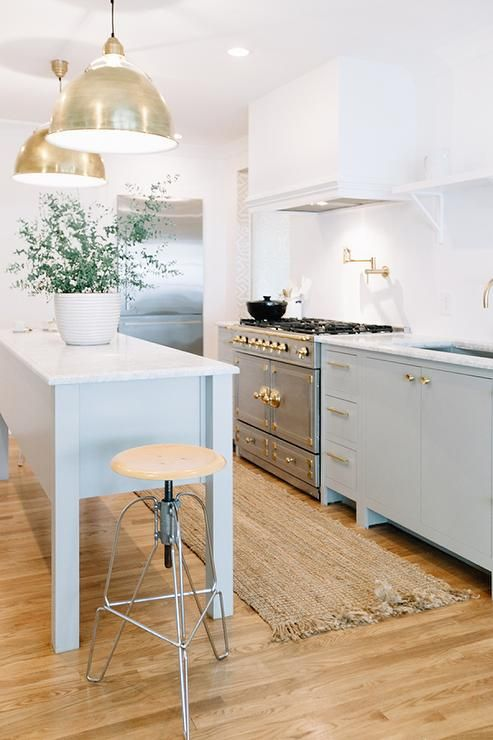 Beautiful kitchen features a gray freestanding island topped with white marble illuminated by a ...