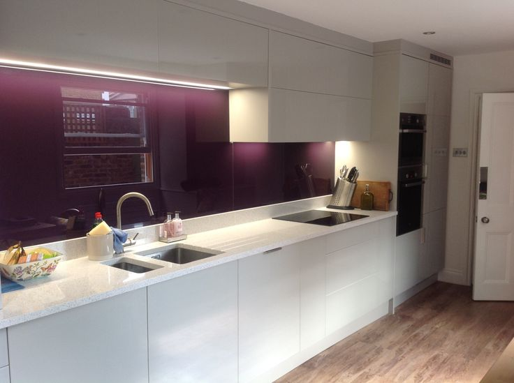 Aubergine glass splash back lifts the white kitchen. Kitchen Cabinets by Kestrel Kitchens