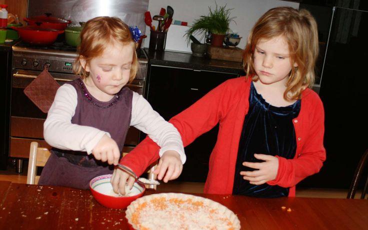 Ferieke en Annemijn strooien de geraspte kaas over de taart met zoete aardappel en appel.