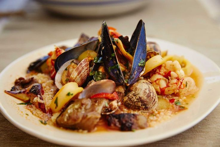 In western Sicily, couscous is often served as an appetizer. Here, a bounty of local seafood—swordfish, shrimp, calamari, and mussels—is piled on top for a hearty main course. The cooking liquid, a fragrant tomato-seafood broth, is rich and flavorful, so be sure to serve the seafood and couscous doused with plenty of it—the couscous will soak much of it up.