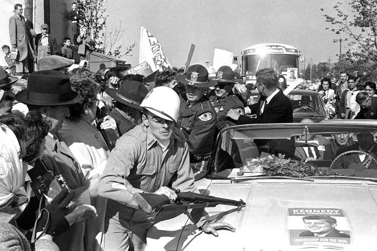 Helmet askew, rifle definitely not at the ready, man in military uniform is jammed against fender of car bearing the Democrats' presidential nominee, on October 25, 1960 in Elgin, Illinois.