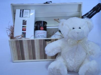 A cute corporate gift hamper. Comes with Frankie the teddy bear, a large 750ml bottle of Champagne, a box of chocolate coated peanuts and plums in port. It also comes in wooden wine keepsake box.