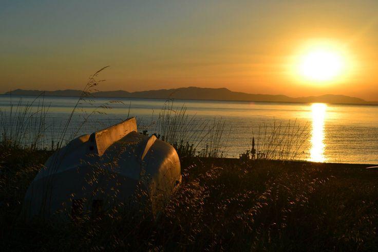 Sunrise over a boat on the beach at Psaropouli, Vassilika, Greece...