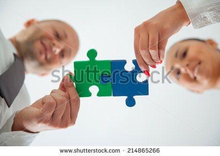 Teamwork - business people assembling jigsaw puzzle