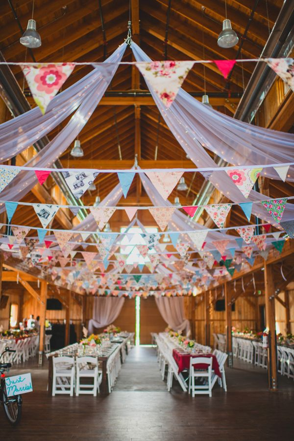 Banderines y telas blancas para decorar el techo en una boda