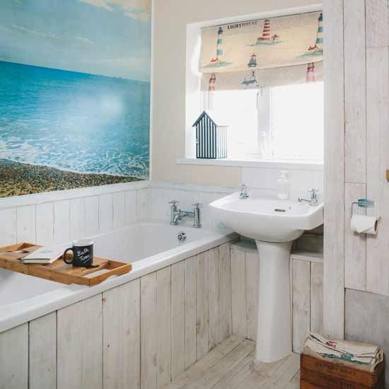 Evoke wonderful memories of summers spent in beach huts with a stunning photo of a seaside landscape positioned above the bath