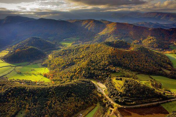 Los volcanes de la Garrotxa, en Girona, son un lugar estupendo para dar un paseo en globo. Las vistas desde las alturas te transportan a un mundo pasado, casi de ciencia ficción, en el que los dinosaurios campaban a sus anchas entre valles y montañas. Cuando el verde que cubre los volcanes empieza a tornarse dorado, es el momento de alzar el vuelo.