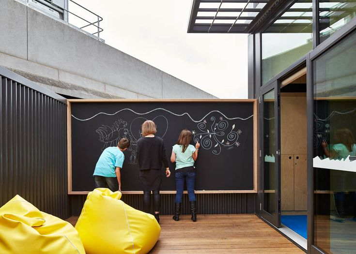 Blackboard on the balcony in the Cubbyhouse at Broadmeadows Children's Court with yellow bean bags | Cubbyhouse by Mihaly Slocombe (2014-15) | Broadmeadows, Victoria, Australia | Photo: Peter Bennetts