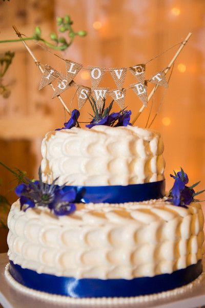 """Petite, two-tier wedding cake with textured frosting, blue ribbon and """"love is sweet"""" bunting topper {Smith Studios Photography}"""