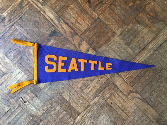 VINTAGE SEATTLE PENNANT, UNIVERSITY OF WASHINGTON PENNANT FLAG, PURPLE AND GOLD WOOL FELT PENNANT  Early University of Washington pennant. Striking color, displays beautifully. Thick felt, perfectly softened and worn. Color still very rich and bright, no fading from sun. Iconic University of Washington deep purple and gold. Raised felt letters, stitched on. Quality construction, tight machine stitch. Ties and tail still intact and in good shape. Dates to the 1920s or 1930s. Good vintage…