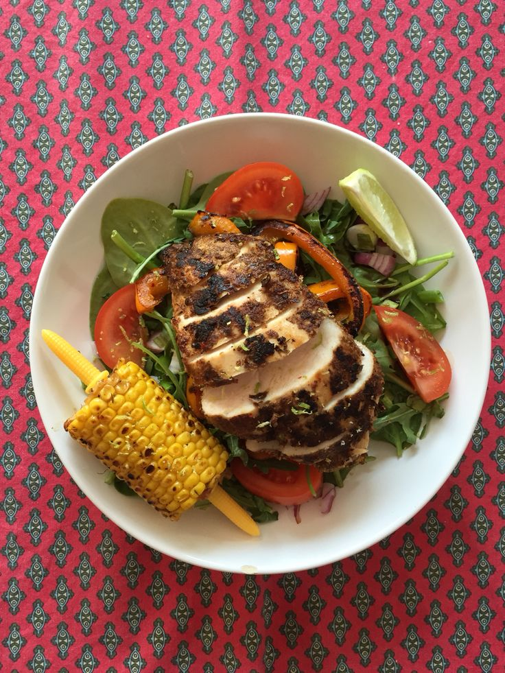 Cajun Chicken Breast with grilled peppers and onions on a bed of mixed salad with a salted corn on the cob to go with it.
