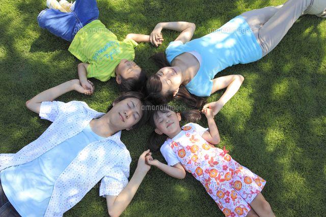 芝生で手をつなぎ寝転ぶ家族 (c)mon printemps