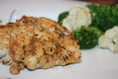 Grilled grouper-4 tbsp butter; 3 cl minced garlic;  1tbsp Parmesan; 1 tbsp herb;  4 tbsp evoo;  1 (3 1/2 to 4 lb) grouper, scaled; l/4 cc finely chopped shallots, basil;  combine the butter, garlic, Parmesan, Essence, and olive oil and whisk; Baste the grouper filets--. Close the grill cover and cook for 3 minutes. Open and brush again with the melted butter mixture. Repeat this process until the flesh is firm and opaque, for a total cooking time of about 12 to 15 minutes for this size fish.