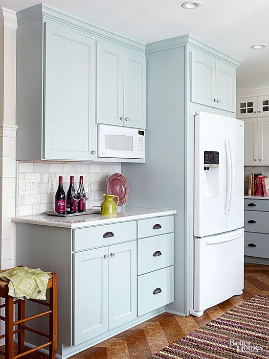 The new entertaining zone and prep station, outfitted with a recycled-glass countertop, includes a built-in microwave and plenty of storage for food and paper goods. Framing a standard-depth refrigerator with cabinetry makes it look like an expensive built-in./